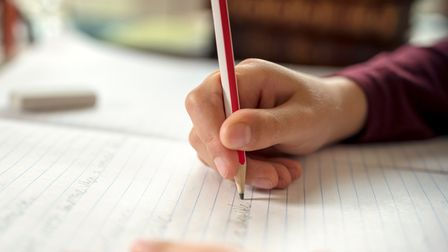 A generic photo of a child writing in a school book. See PA Feature HEALTH Dyslexia. Picture credit