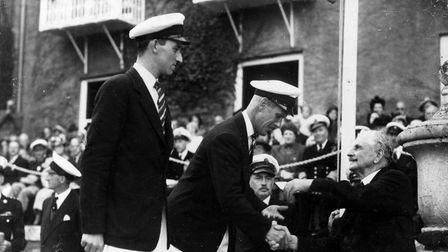 Sir Ralph Gore presents helmsman Stewart Morris and crewman David Bond the gold medal for their success in the Swallow Class.