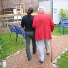 younger woman accompanying older woman walking on a pathway heading towards some seating