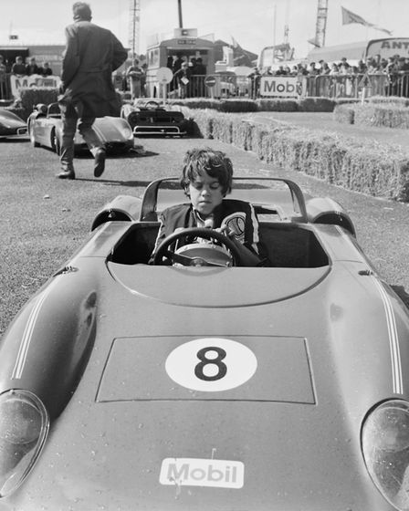 Chad McQueen drives a small Ferrari during the shooting of the film Le Mans with father Steve McQuee