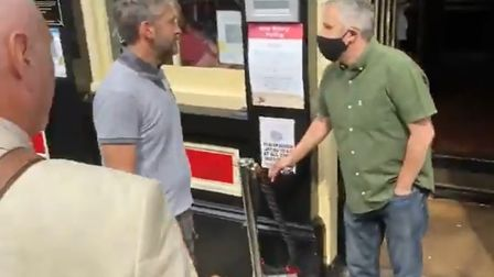 Still from video showing protesters confronting Murderers landlord Phil Cutter.