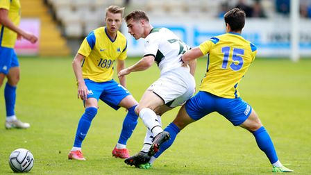 Adam Randell of Plymouth Argyle battles for the ball with Trialist of Torquay United during the pre