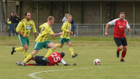 Ruel Fox making a tackle as Grant Holt watches on - The NCFC legends v NHS staff match taking place