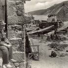 A old manposes outside among the boats in Sennen Cove, circa 1928