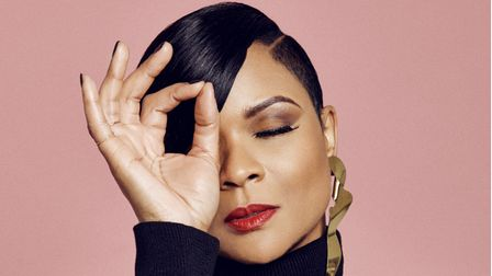 Singer Gabrielle in a black top with her right hand up to her face