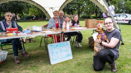 A raffle table and woman with a dog at a community fun day fundraiser on The Common, Saffron Walden, Essex