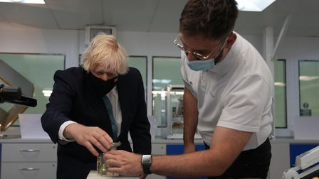 Prime Minister Boris Johnson (left) is shown the workings of ADTM mechanism, which adjusts the refle