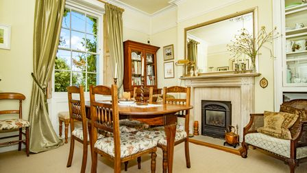 grand-looking dining room with cream walls, white-barred sash window, white timber fire surround with iron gas fire, mirror