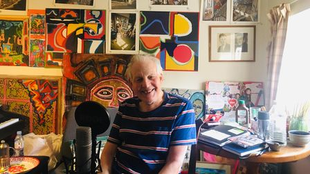 Piers Plowright pictured in a studio full of his artwork