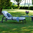 A chaise lounge in a luscious garden with a low table beside it. On the table is a glass of juice
