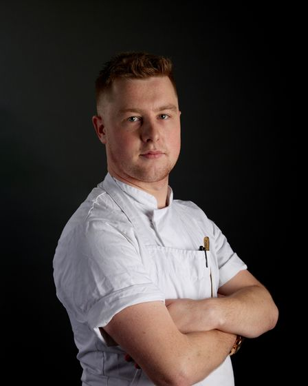 In front of a black background, Alex Webb looks towards the camera, his arms crossed.