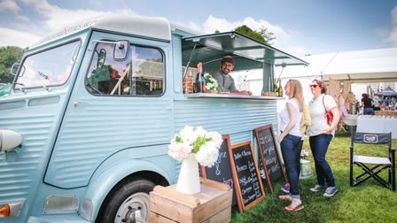 A pastel blue food truck has its hatched open and a man take orders from two patrons