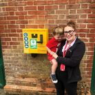 Grasshoppers Day Nursery practitioner Faye Clements with one of the children at the site of the new defibrillator.