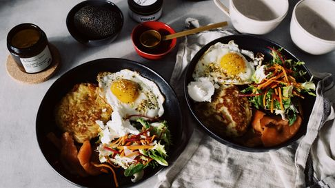 Two bowls loaded with brunch foods sit on a table with coffee cups