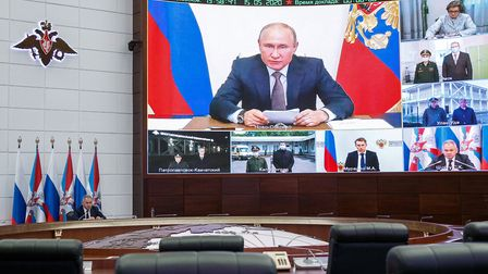 Russia's Defence Minister Sergei Shoigu (L) and Russia's President Vladimir Putin (on the screen) du