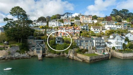 A view from the opposite side of the River Dart, the property is nestled in trees high above the water