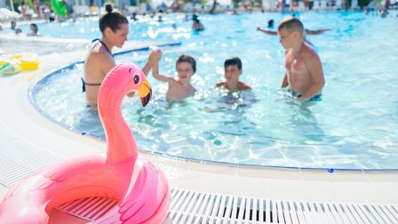 A pink inflatable flamingo ring sits by the side of a busy pool where children splash around