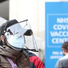 A person wears a plastic face covering as they wait in line for the Covid-19 vaccinations at the Olympic Centre Wembley