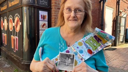 Linda Ashwood holds a photo of herself aged 15 in the same spot, when she first began working at Langleys