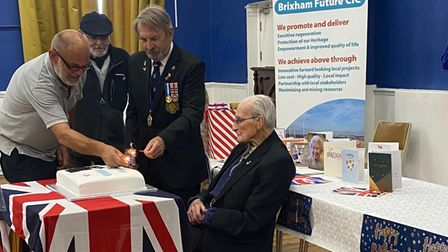 Fred Bates, seated, is helped to distribute the birthday cake to 50 people on his 105th birthday.