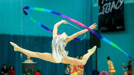 Rhythmic gymnasts performing at a competition