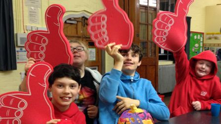 A group of children happy and smiling at an Accuro event in west Essex. They hold big foam 'thumbs up' in the air.