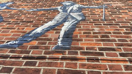 Close up of art work: man dancing with a cane.