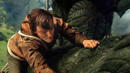 Actor Nicholas Hoult as Jack the Giant Slayer climbing a beanstalk with Cheddar Gorge beneath him