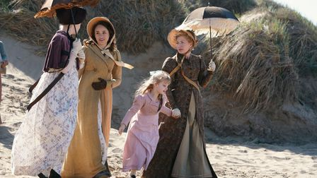 Actors, including a young girl, in Edwardian outfits including bonnets and parasols strolling along a beach
