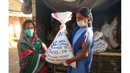 Two women in India holding food parcels