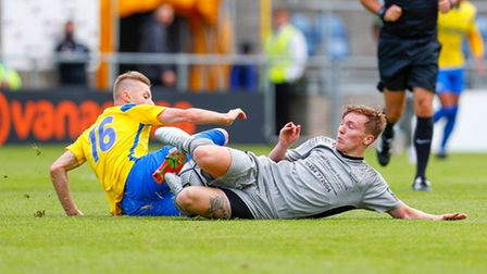 Keelan O'Connell of Torquay United challenges for the ball with Luke Russe of Chippenham Town during