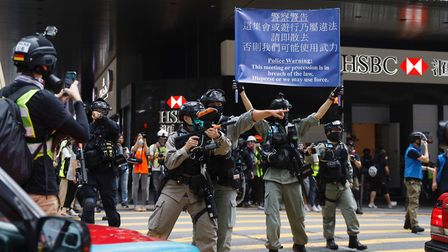 Hong Kong police massed outside the legislature complex ahead of debate on a bill that would crimina