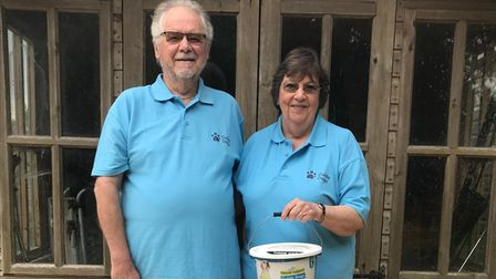 Roger and Christine Goss in blue Norwich Guide Dog fundraising polo shirts with their guide dog Rupert