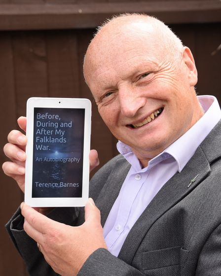 Former marine Terence Barnes from Ipswich, with a digital version of his book about his time serving