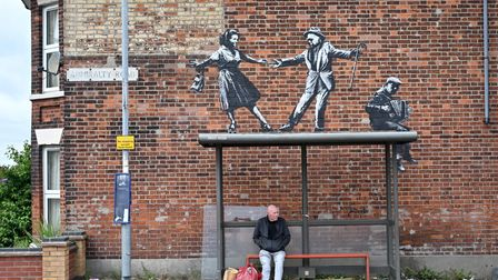 A man waits at a bus stop below a Banksy artwork of a couple dancing to an accordion player in Great Yarmouth