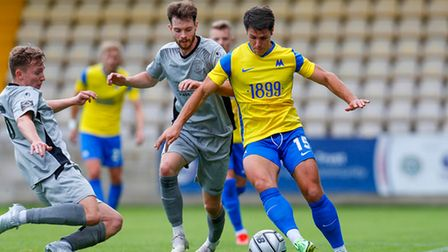 Dan Holman of Torquay United battles for the ball with Alex Bray of Chippenham Town and Luke Russe o