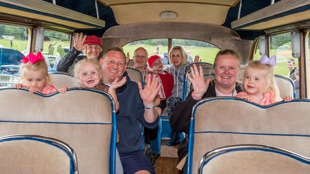 A group of people sat towards the back of a vintage bus at Saffron Walden Motor Show. They smile and wave.
