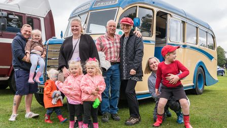 A large group of people - adults and children - in front of a vintage cream and blue bus at Saffron Walden Motor Show