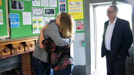 A Level results joy at Gosfield School, Cut Hedge Park, Halstead, Essex: student hugging a woman, watched by a man