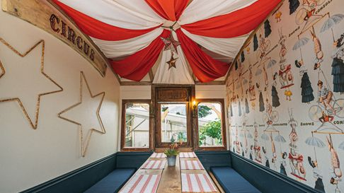The carriages and double decker bus where tables are placed are decorated in quirky designs