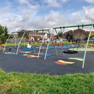 A photograph of Golden Acre in Saffron Walden, Essex with new-looking swings and play equipment after a refurbishment