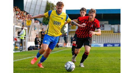 Gabby Rogers of Torquay United battles for the ball with Aaron Roberts of AFC Bournemouth U21s