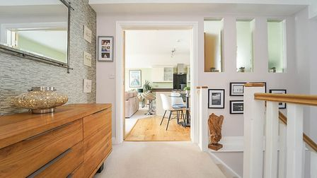 landing of the house in Cecil Road Weston, three arrow-slit windows looking into kitchen, sideboard and white bannister