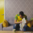 A still from Norwich City's kit launch video showing Lukas Rupp on the sofa which has been donated to The Benjamin Foundation