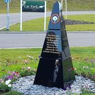 A pyramid-shaped memorial complete with flowers - a Covid-19 memorial at Cam Valley Crematorium