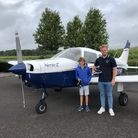 boy and man stood in front of light aircraft
