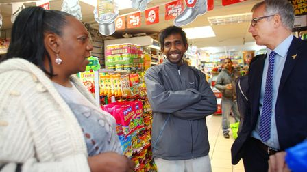 Pauline Pearce and Brian Paddick (right) chat to shopkeeper Siva Kandiah, whose store was looted dur