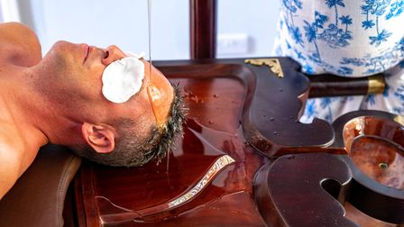 Picture shows a man lying down on a wooden treatment table while oil is poured slowly over his forehead