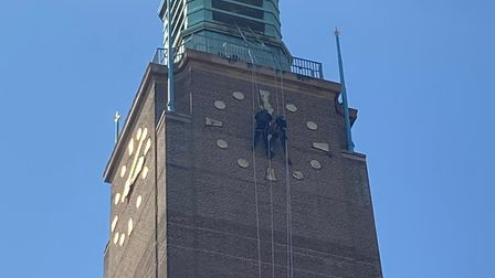 Contractors in action replacing the hands on City Hall's Clock Tower