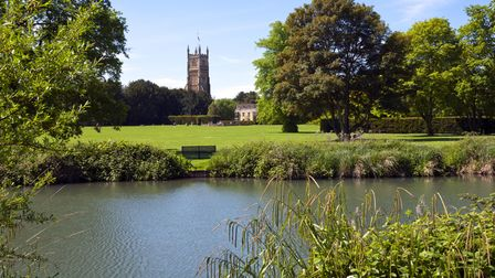 Tower of the landmark Abbey Church seen across Abbey Grounds in spring sunshine, Cirencester, The Co